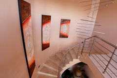 Stairs leading up. To upper bedroom in upmarket South African home, paintings on wall with chandeliers Stock Images