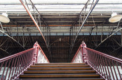 Stairs leading up under an old truss roof Stock Photography