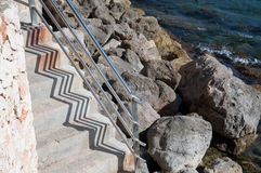 Stairs by the Mediterranean sea with rocks and zigzag shadow pattern Stock Photo