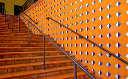 Stairs near colorful wall. Wide red brick stairs with metal railing separation near a colorful orange tile wall. The wall is decorated with white and blue royalty free stock photos