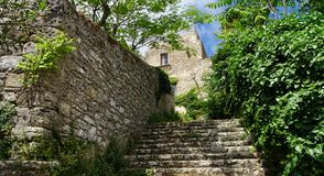 Stairs next to stone wall to a house of stone royalty free stock photography