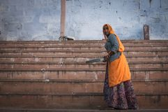 By the stairs. Pushkar, India : 17th February, 2015 - A shot of an Indian lady in traditional clothing by the stairs at Pushkar Lake, India Royalty Free Stock Photo