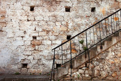 Stairs with railing against the old stone walls Stock Photo