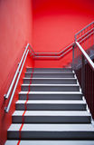 Stairs and red wall. Stairs in a red-painted hallway Stock Photos