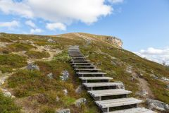 Stairs rise up to the mountain. Beautiful blue sky and clouds. Lapland. royalty free stock photo
