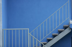 Stairs with Safety Railing against Blue Wall. Stairs with Handrails as Safety Feature with Beautiful Blue Wall in Background Stock Photos