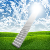 Stairs in sky with green grass, clouds and sun Stock Photo