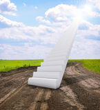 Stairs in sky with green grass, road and clouds Stock Image