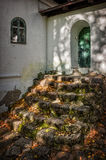 Stairs. Steps from a moss-covered rocks to a small door Royalty Free Stock Images