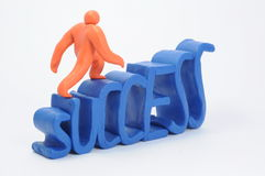 Stairs of success. A plasticine orange man climbs a stairs looking like lettering success stock image