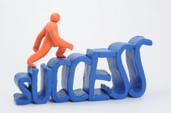 Stairs of success. A plasticine orange man climbs a stairs looking like lettering success. An another view Stock Photos
