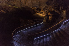 Stairs to the dark. Low illuminated long, curved, wet and slippery stone stairs leading to a big dark prehistorical cave Royalty Free Stock Photos