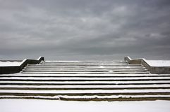 Stairs to heaven. Snowy concrete stairway leading to moody cloudy sky Stock Images