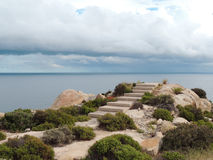Stairs to Nowhere. Dark, gloomy day. Deserted area with thorn-bushes and rocks. Storm clouds over the sea. This is the site of a launched and abandoned left Stock Image