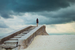 Stairs to nowhere - lonely figure. Stairs to nowhere; A female figure climbs a series of old forgotten stone steps on a deserted beach; Can convey a sense of stock image