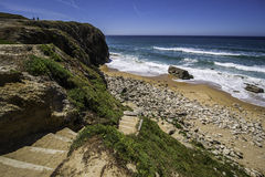 Stairs to rocky beach with sand and waves in daytime Royalty Free Stock Photography