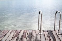 Stairs to the sea or lake and wooden deck. Stairs on a pier, to the water, with text space Stock Images