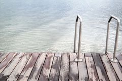 Stairs to the sea or lake and wooden deck. Stairs on a pier, to the water, with text space Stock Image