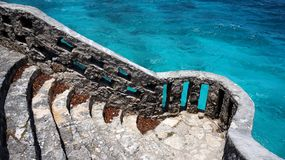 Stairs to the sea. An old stone stairway leading to a viewpoint over the beautiful turquoise ocean stock photo