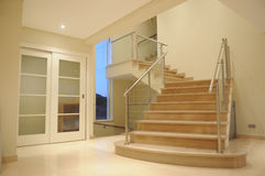 Modern Marble Staircase - Interior Mansion Lobby. Stone stairs of white and pink marble of a lobby in a villa. White wooden wardrobe to guests use. Built by Stock Photos