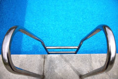 Stairs to the swimmingpool. And blue water Royalty Free Stock Photos