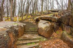 Stairs up among stone granite boulders in the park with trees without leaves. Autumn melancholic landscape on the background gray. Rainy sky Royalty Free Stock Images