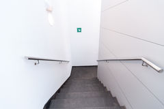 Stairs. Wth a metal railing between a white wall Stock Image