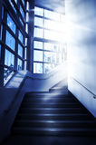 Stairway. A stairway winds around a corner with a bright light at the top of the stairs Stock Image