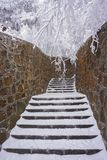 The stairway covered by snow and was braced by rock wall ,among with trees covered by snow stock photos