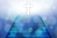 Stairway going up to the christian cross. With bokeh light background,blue color tone stock photography