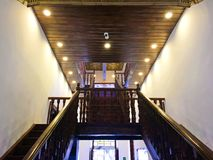 Wooden Staircase and Ceiling in Historic Building, Cuenca Ecuador. The stairway of the Museo Remigio Crespo Toral. Bright lights from the dark brown ceiling stock photos