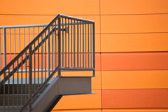 Stairway and Orange Wall. A modern staircase and platform with stainless steel railing against an orange wall royalty free stock image