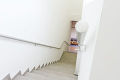 Stairway with railing is going down in a new modern building. Royalty Free Stock Image