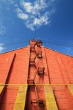 Stairway on red brick wall on clear blue sky. Vertical Stock Photography