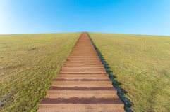 Stairway to heaven. Huge stairway leading to the top of a green hill Royalty Free Stock Photo