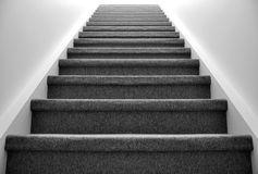 Stairway to heaven. Black and white view up a carpeted staircase leading into light Royalty Free Stock Image