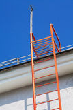 Stairway to heaven. Bright red pompier ladder leading to a roof and an azure summer sky above stock images
