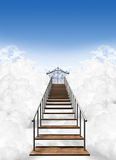 Stairway To Heaven. A depiction of the stairway to heavens pearly gates above the clouds on a clear blue sky background Stock Photo