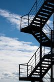 A fire escape against a cloudy sky royalty free stock photography
