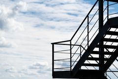 A fire escape or an external staircase on a building silhouetted against a cloudy sky royalty free stock image