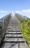 Stairway to heaven - steel staircase going up to a blue sky with clouds Stock Photography