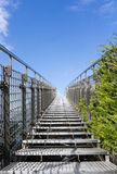 Stairway to heaven - steel staircase going up to a blue sky with clouds Royalty Free Stock Photography