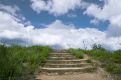 Stairway to heaven. Stone stairs, sky, clouds and grass Royalty Free Stock Photos