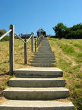 Stairway to home. Long haul of steps up grass bank to house at the top Royalty Free Stock Photography