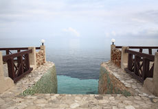 Stairway to Paradise. Steps leading into the Caribbean Sea, merging with the sky, at dusk Stock Photo