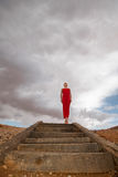 Stairway to the sky. Young woman in red dress standing at the top of wooden staircase with dark clouds in the background Royalty Free Stock Photos
