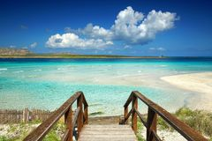 Stairway to turquoise water and white sand beach lagoon Royalty Free Stock Photo