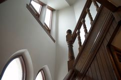Stairway View. An open stairway in a very old church shows wooden bannisters, high ceilings and windows Stock Photos