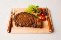 Stake. Appetizing stake with tomatoes on a wooden plate Royalty Free Stock Image