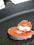 Stake of salmon on pan Stock Photos